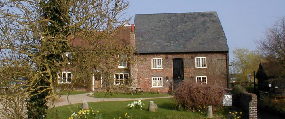 Redbournbury Watermill in early spring, with daffodils in the garden
